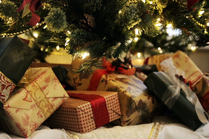 A set of presents under a warmly lit christmas tree