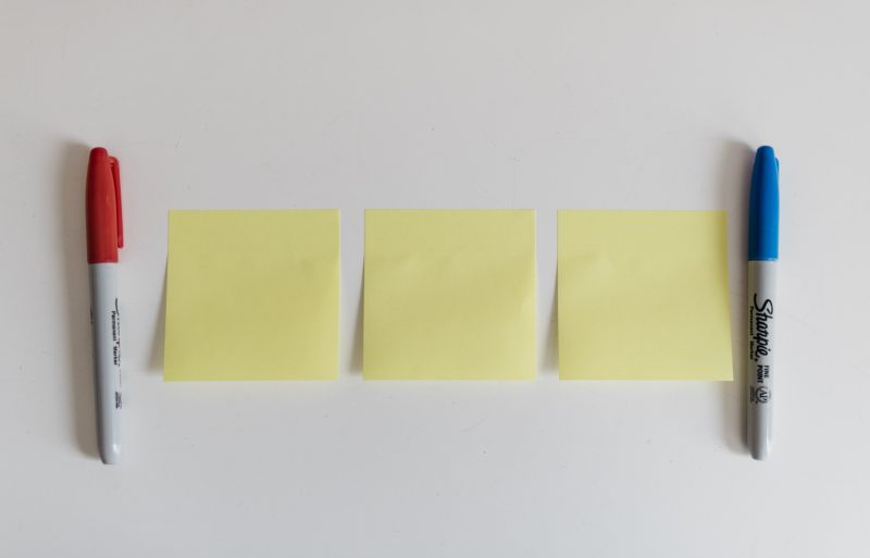three post-it notes on the wall, with a pen on either side