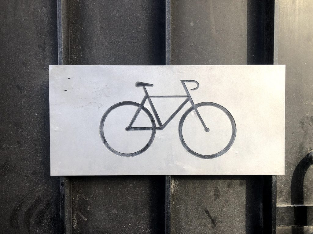 The symbol of a bicycle on a metallic plate on a door.