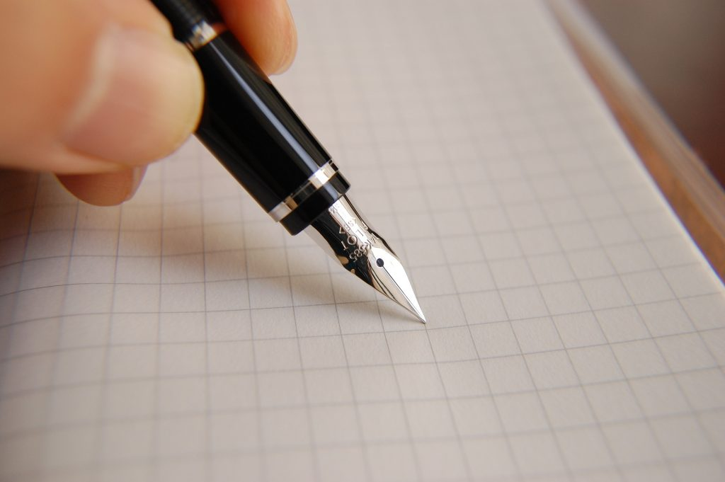 An ink pen with a sharp metallic tip is poised over squared paper