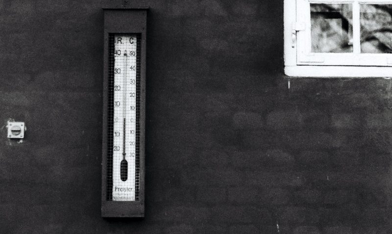 A thermometer on a black wall. A play on the words