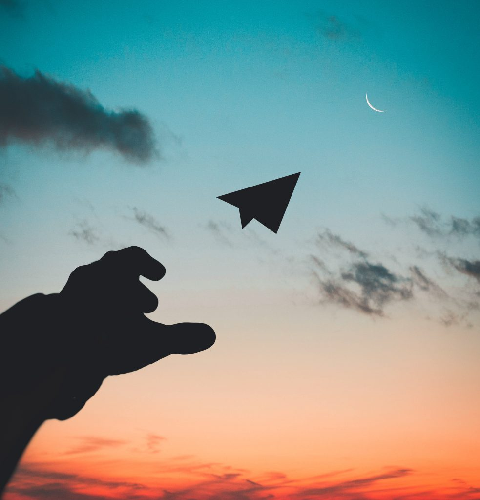 The silhouette of a hand throwing a paper airplane into the orange blue sky.