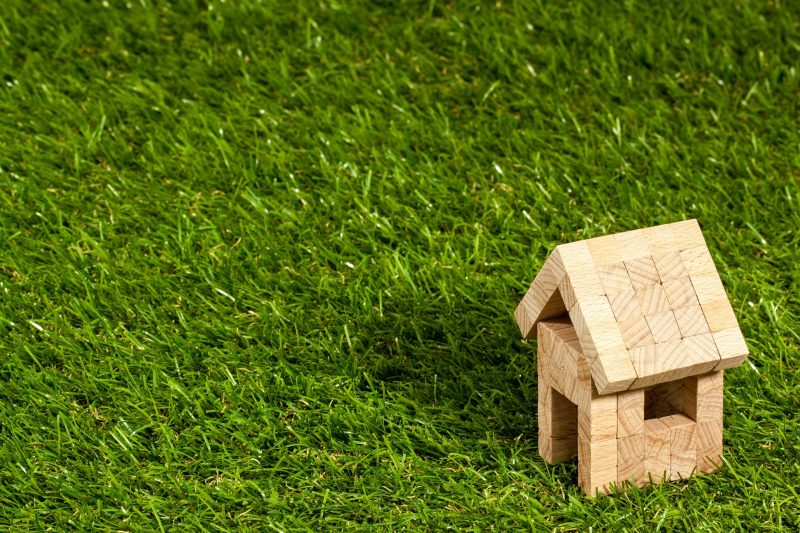 A little wooden house made of blocks set down in the green grass
