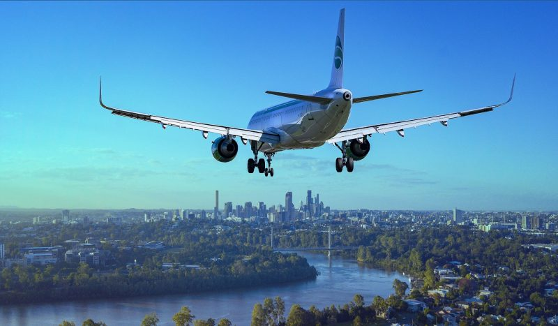 An airplane flying towards a big city in a bright blue sky